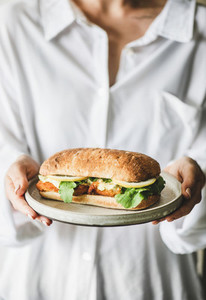Woman in white shirt holding breakfast sandwich with fried fish