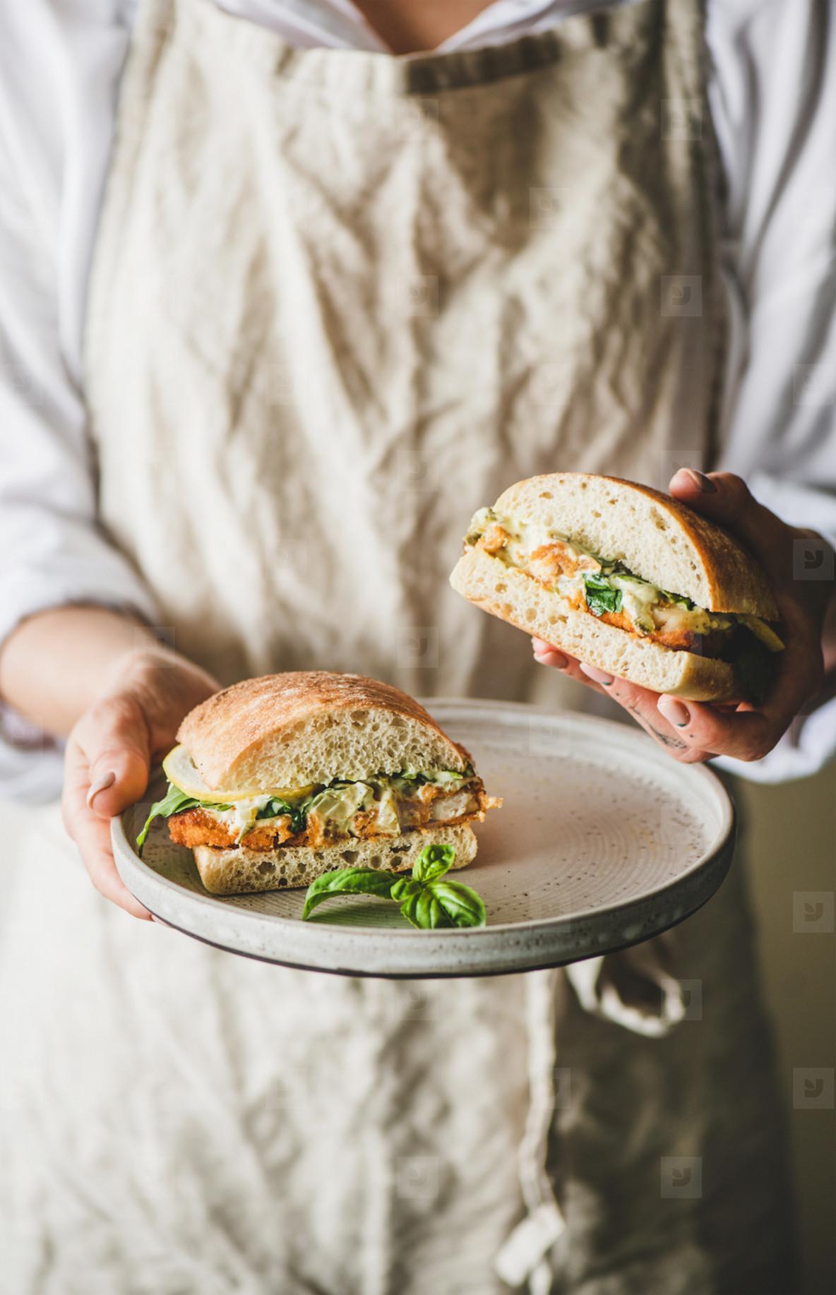Woman holding fresh breakfast sandwich with fried fish  lemon  arugula