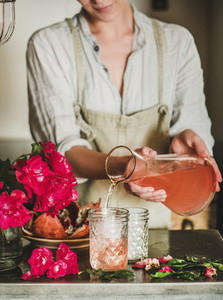Young woman pouring rose lemonade to glasses over kitchen counter