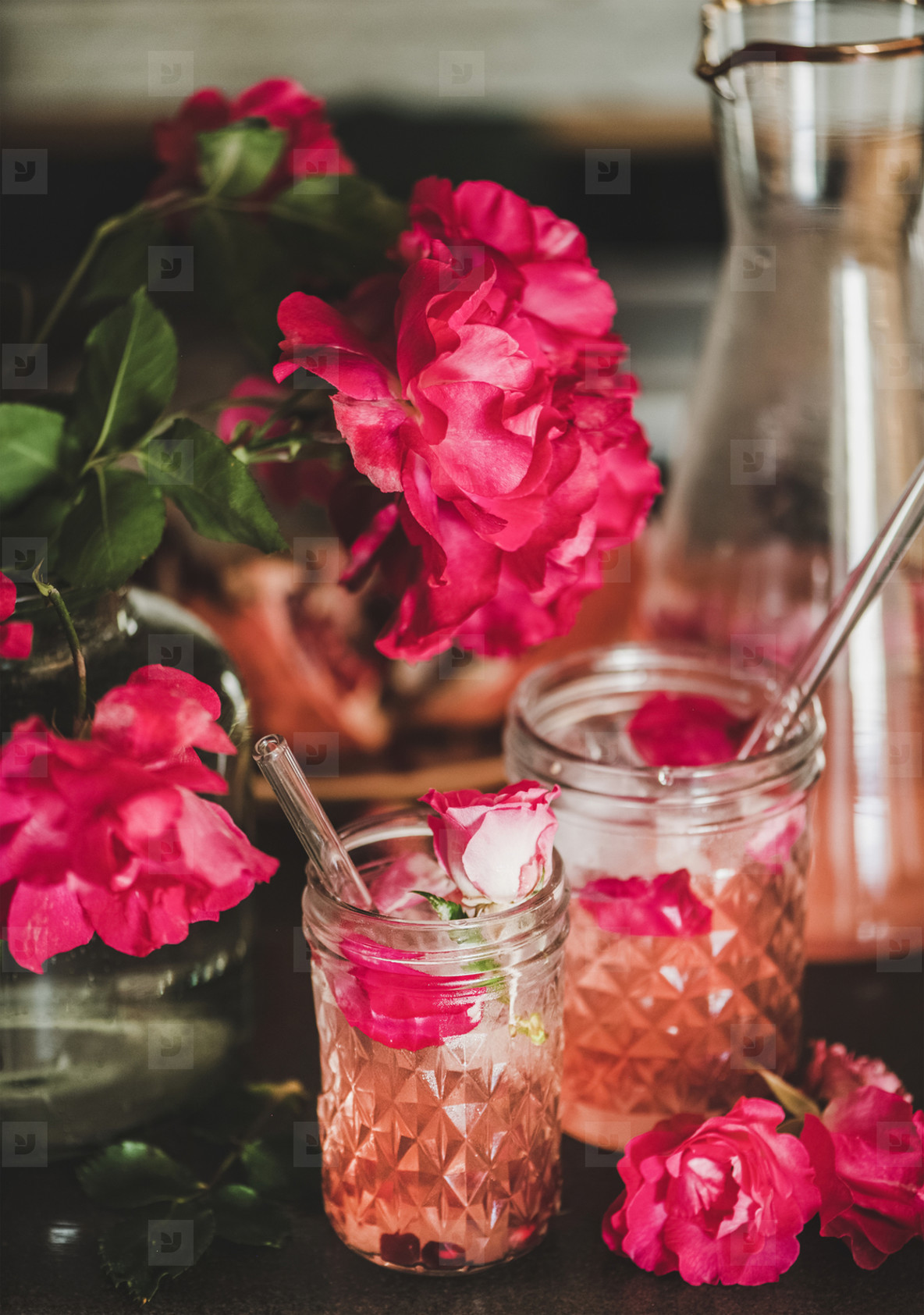 Rose lemonade with ice and petals over kitchen counter  close up