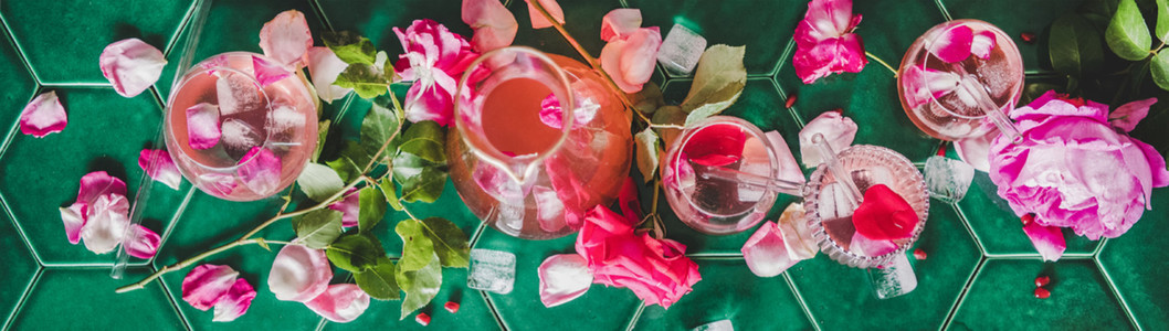 Flat lay of rose lemonade with ice and petals  wide composition