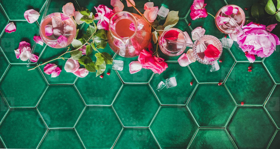 Flat lay of rose lemonade with ice and rose petals