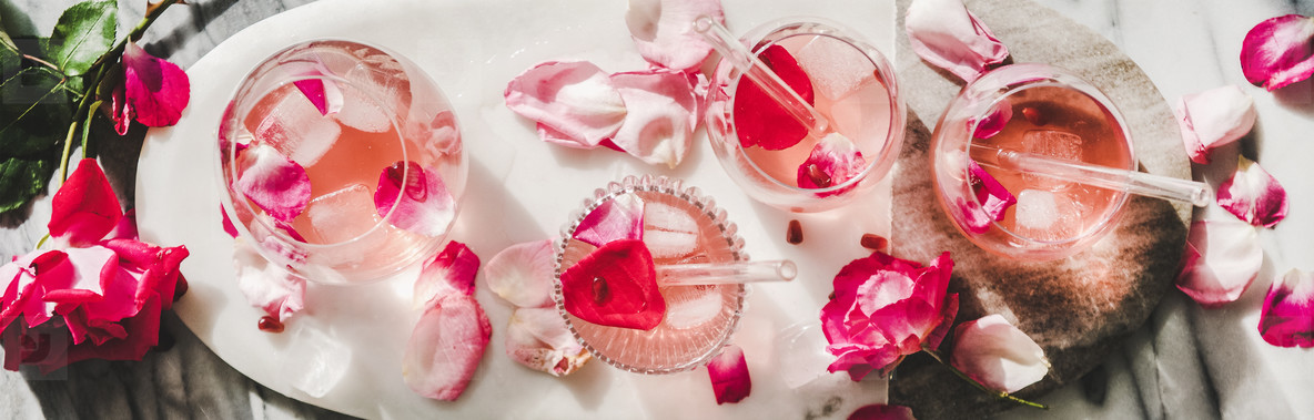 Rose lemonade with ice and pink rose petals  wide composition