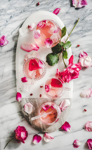 Rose lemonade with ice cubes and pink rose petals
