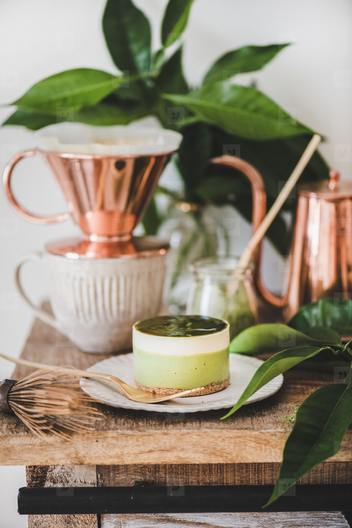 Green matcha cheesecake and coffee in copper pot and mug