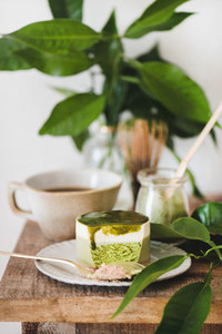 Green matcha cheesecake and black coffee on kitchen counter
