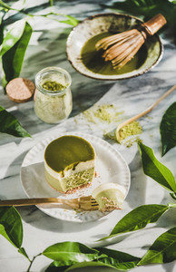 Green matcha cheesecake and leaves over marble table background