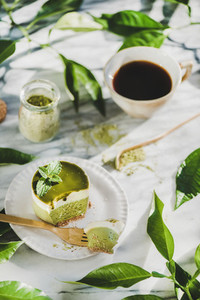 Green matcha cheesecake and black coffee in cup  selective focus