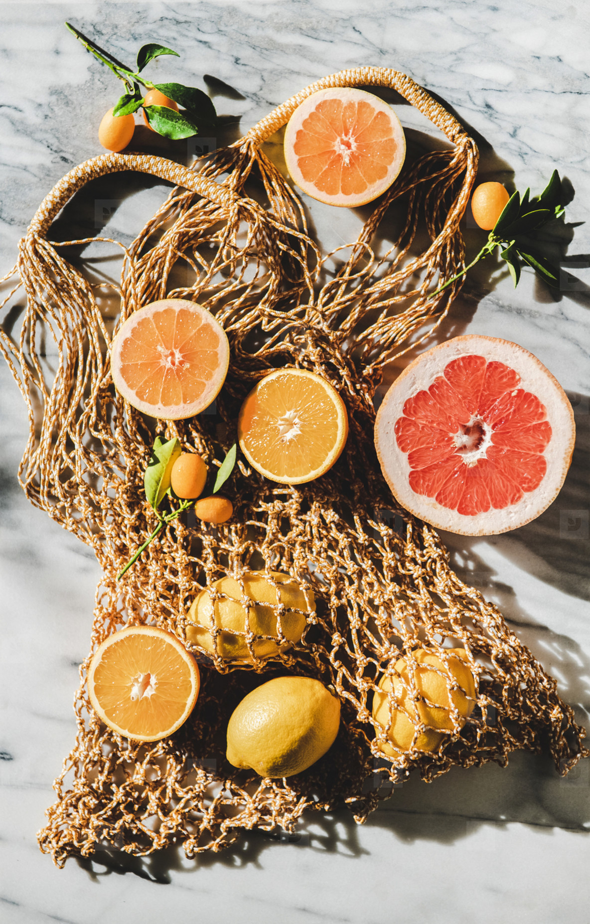 Flat lay of summer net bag with fresh ripe citrus fruits