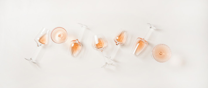 Flat lay of rose wine in glasses over plain white background