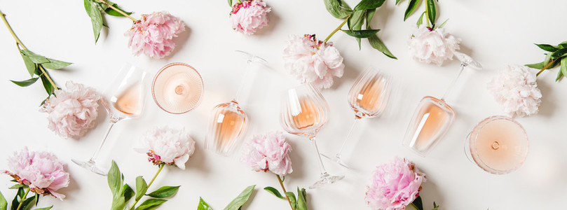 Rose wine in glasses and blossom peonies over white background