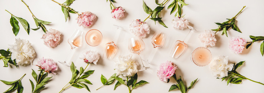 Rose wine in different glasses and blooming summer peony flowers