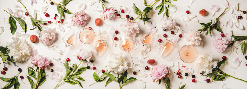 Rose wine in glasses with flowers and summer fruits