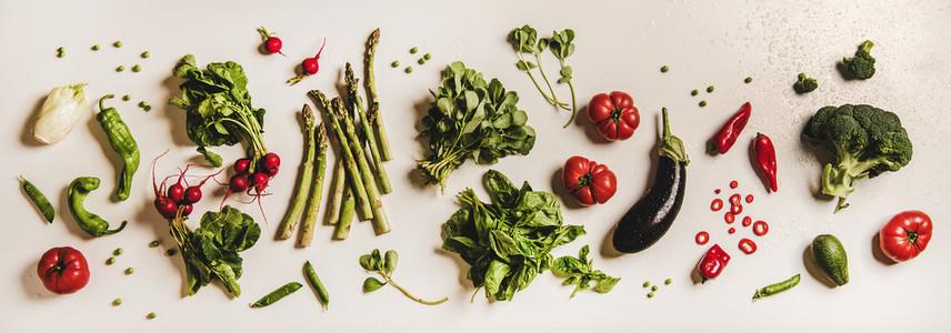 Flat lay of various summer fresh vegetables over plain white background