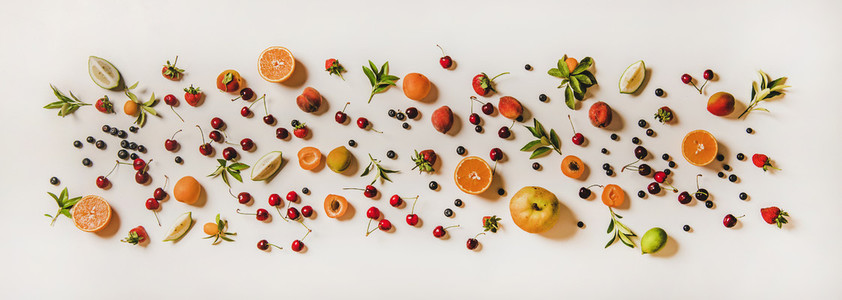 Flat lay of various summer fruits and berries over white background