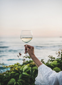 Woman holding glass of wine with sea and sunset background