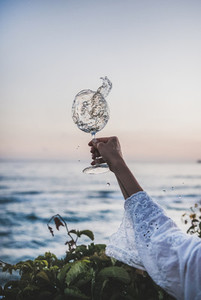 Woman holding glass of white flowing wine with sea background