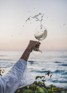 Woman flowing white wine from winelgass over beautiful sunset