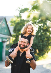A little daughter sits on the shoulders