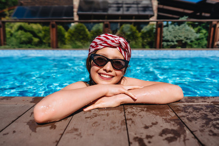 Girl teenager in a pool side looking at camera