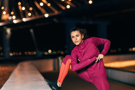 Middle east woman doing flexibility exercises outdoors at night