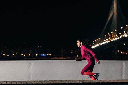 Woman runner at night  Sportswoman sprinting outdoors against a bridge