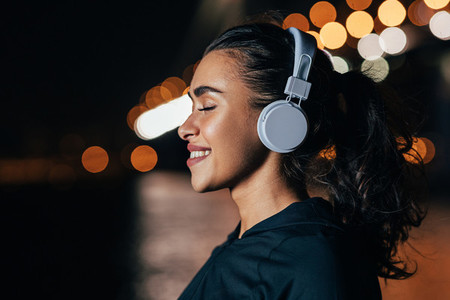 Close up of smiling woman in headphones standing against night city lights