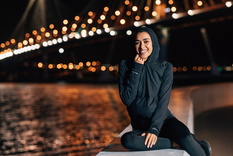 Beautiful middle east woman in hoodie sitting on embankment at night and resting after workout