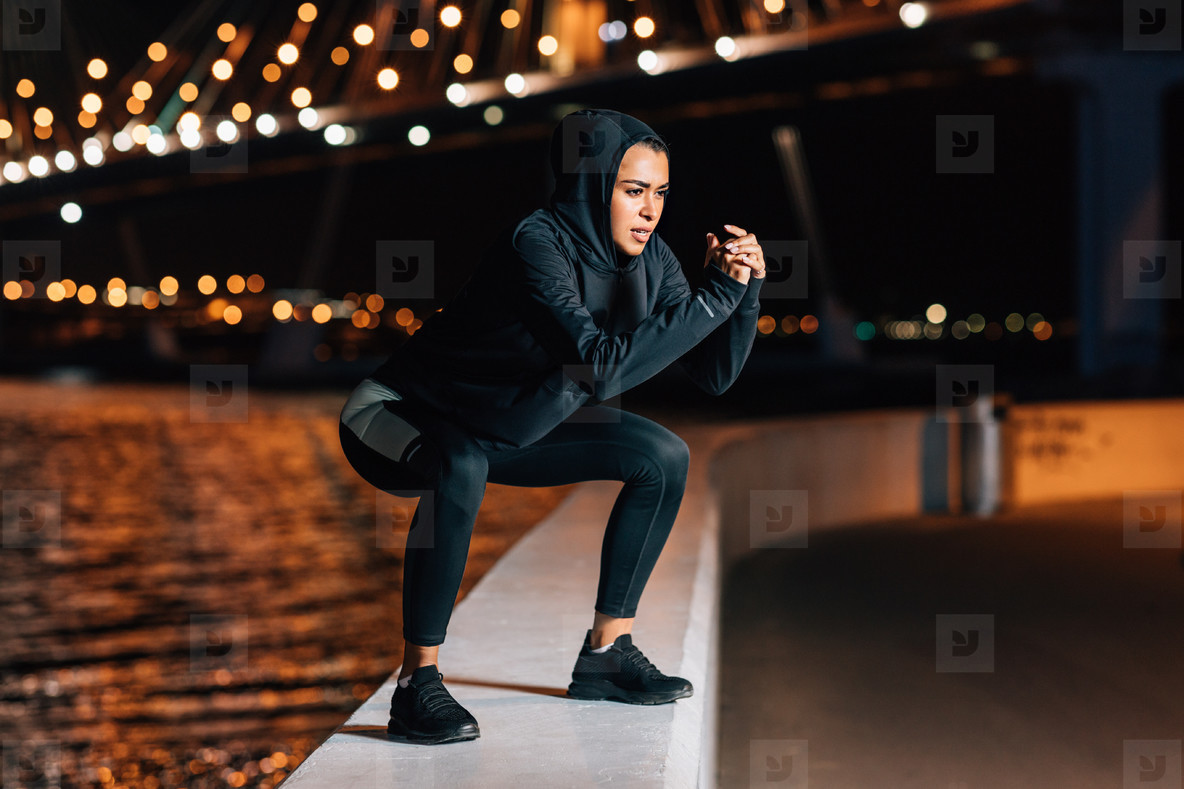 Woman in hooded sport shirt doing squats on embankment at night