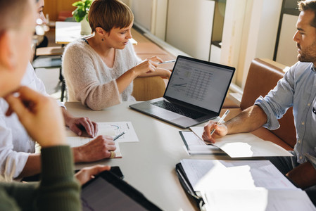 Manager showing figures on laptop to colleagues in meeting