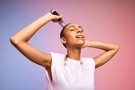 Androgynous female shaving her head