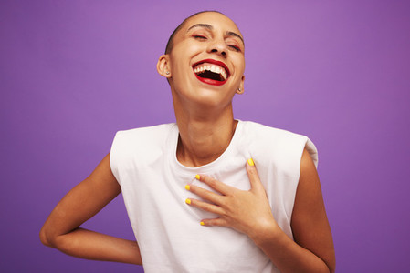 Pretty female model laughing on purple background