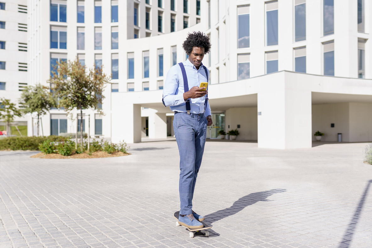 Black businessman on a skateboard looking at his smartphone outdoors