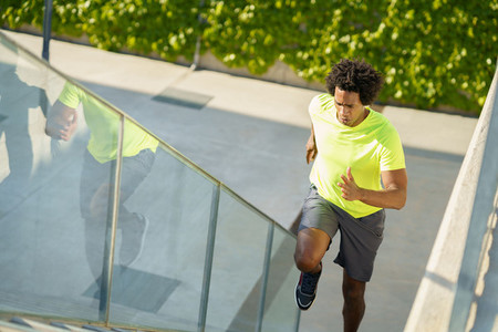 Black man running upstairs outdoors  Young male exercising