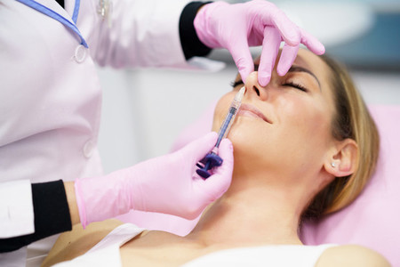 Doctor performing rhinoplasty by injection of hyaluronic acid in the nose of his patient