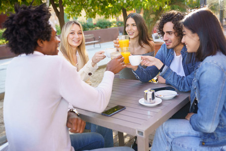 Multi ethnic group of friends toasting with their drinks while having a drink together