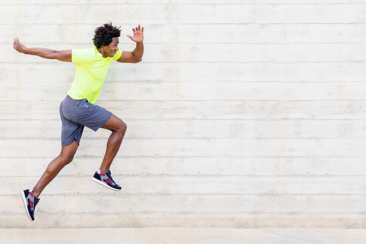 Black man training running jumps to strengthen his legs