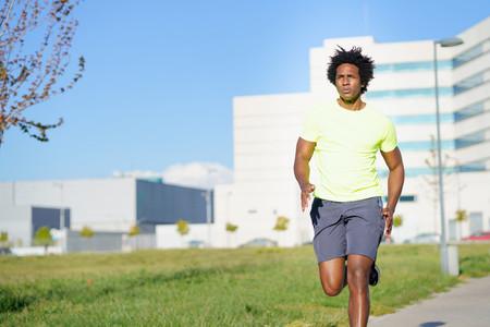 Black athletic man running in an urban park