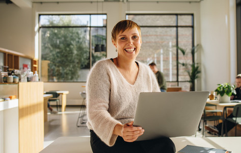 Smiling entrepreneur in co working space with laptop