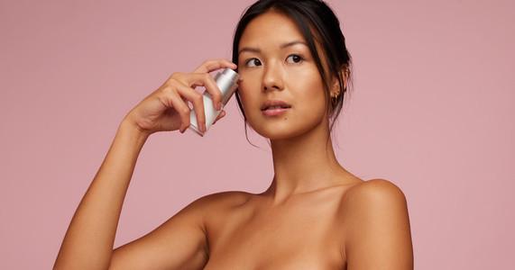 Beautiful woman applying skincare serum on her face