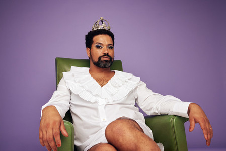 Confident drag queen sitting on arm chair