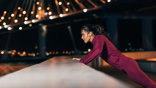 Side view of young middle east woman doing push ups  Female athlete exercising at night outdoors