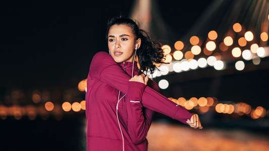 Young fitness woman in headphones stretching her arm at night during a workout