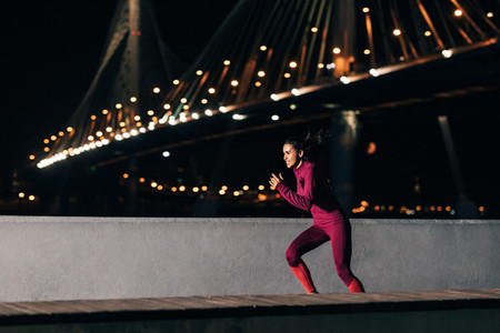 Female runner in sportswear exercising at night  Side view of a woman jogging outdoors at embankment