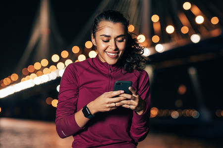 Young female in sportswear typing on smartphone while sitting at night outdoors