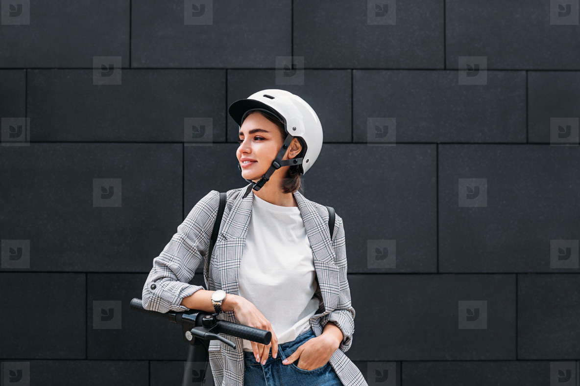 Young woman wearing a scooter helmet standing at a black wall  Smiling female in casual clothes leaning electric scooter looking away