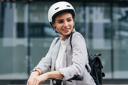 Young businesswoman with electric scooter looking away  Cheerful female in safety helmet wearing backpack standing outdoors