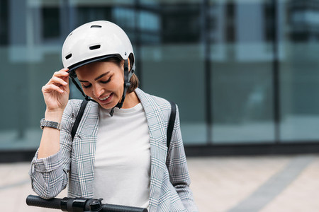 Portrait of a beautiful young woman with safety helmet looking down standing outdoors at office building