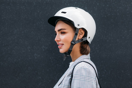 Side view of young woman wearing safety helmet  Female in scooter helmet standing at black wall