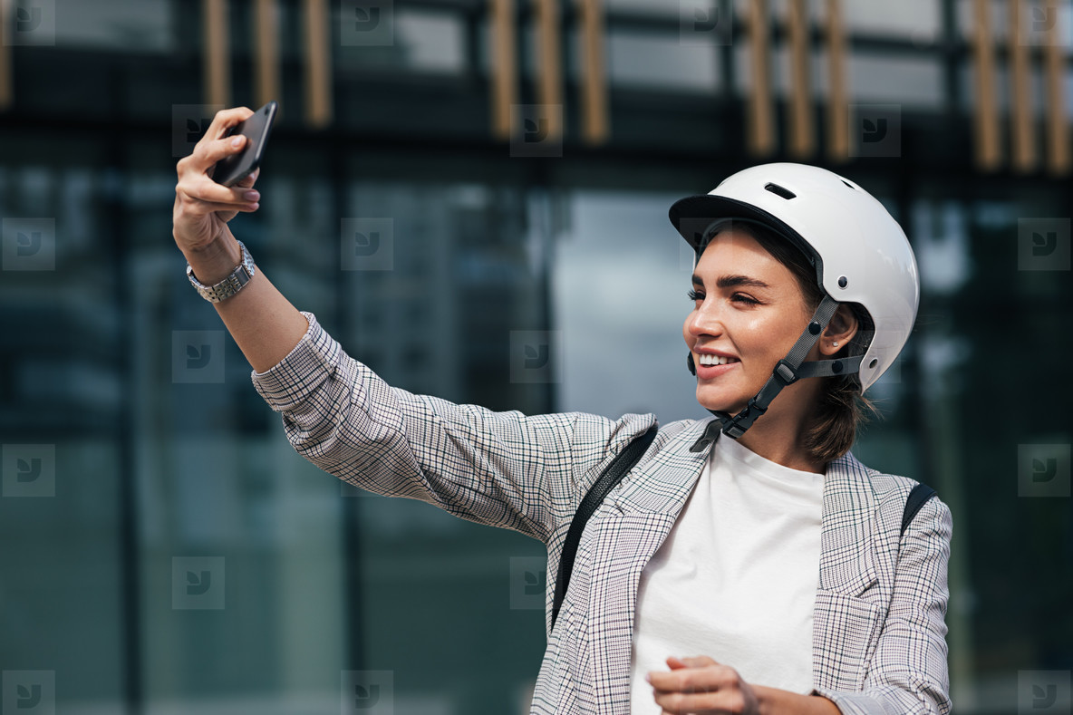 Smiling female wearing safety helmet taking a selfie  Young businesswoman in a white helmet in front of a building